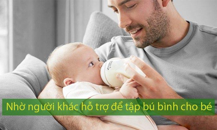 Nhờ người khác hỗ trợ để tập bú bình cho bé, có thể là bố hoặc ông bà nội ngoại